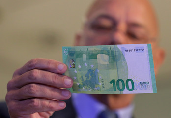 Austrian Central Bank Director Kurt Pribil displays a new 100 euro banknote in Vienna