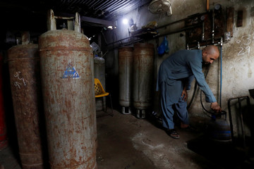 A worker fills a cylinder with liquid petroleum gas (LPG) at a workshop in Karachi,