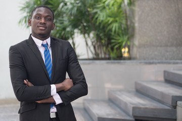 happy and confident african or black businessman; portrait of confident, successful african or black business man, manager, business executive CEO; young adult african man model