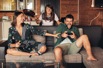 Happy friends playing video games at home