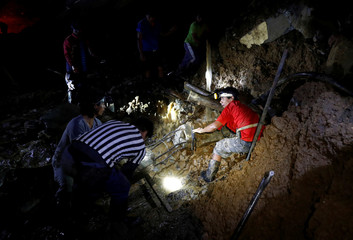 Rescuers search for miners from the rubble of a bunkhouse after a landslide caused by Typhoon Mangkhut at a small-scale mining camp in Itogon