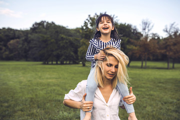 Cute happy little girl laughing and sitting on her beautiful mother's shoulders have fun outdoor in the park. Happy family time together. Positive emotion. Good relationship between mom and daughter.