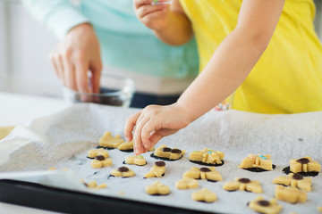 family, cooking and baking concept - mother and little daughter with sprinkles decorating cookies on tray at home kitchen