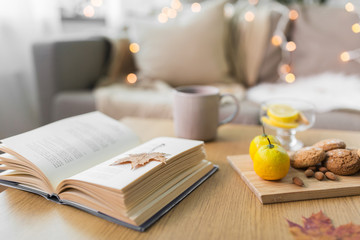 Fototapete - hygge and cozy home concept - book, autumn leaves, cup of tea with lemon, almond nuts and oatmeal cookies on table