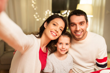 family, christmas and holidays concept - happy mother, father and little daughter taking selfie at home