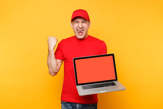 Delivery man isolated on yellow orange background. Professional male employee courier in red cap, t-shirt holding laptop computer with blank empty screen. Service concept. Copy space. Mockup template.