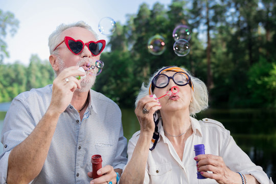 Shiny bubbles. Positive funny senior people standing outdoors and enjoying blowing soap bubbles
