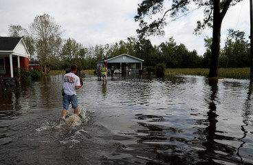 Members of the Marion Rural Fire Department carry supplies to a homeowner flooded after Tropical Storm Florence in Marion