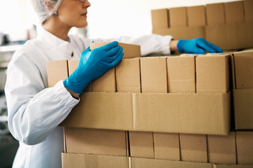 Focused female worker in sterile clothes is counting boxes ready for deliver.