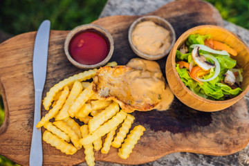 French fries, green salad with champignons and chicken breast. Lifestyle food