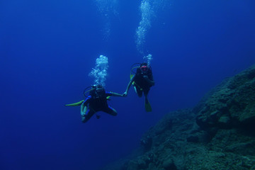 Two divers hold hands as they swim off the island of Sifnos