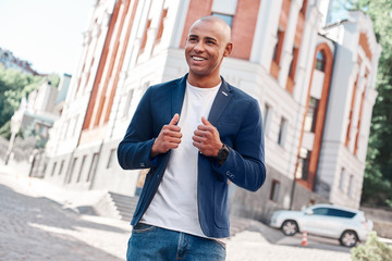Outdoors leisure. Young man walking on the city street touching jacket looking forward smiling cheerful