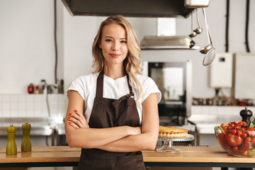 Smiling young woman chef cook in apron