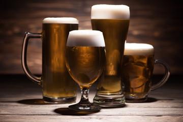 four glasses of tasty beer on wooden tabletop, oktoberfest concept