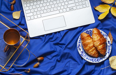 Deep blue autumn concept flat lay with a laptop, fall leaves and a snack. Breakfast in bed top view compostion