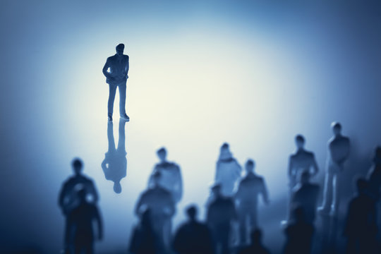 Single man standing in front of group of people.