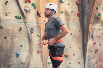 Man climber preparing to climb artificial indoor climbing wall