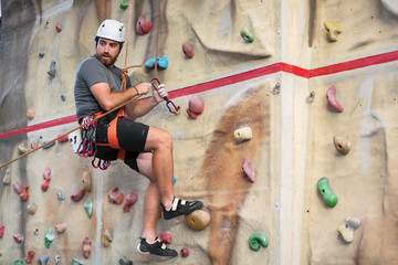 Man climber on artificial climbing wall