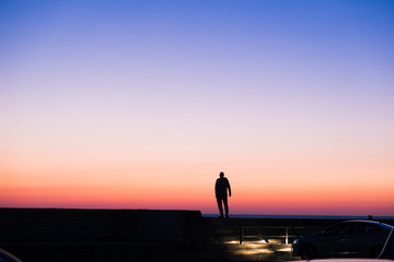 silhouette of a lonely standing man standing against the sunset sky blue with red