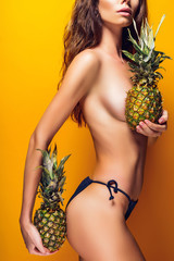 Anonymous young female in black panties holding ripe pineapples near boobies while standing on bright yellow background