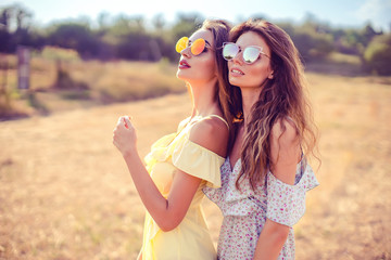 two pretty womem walking in the field dressed in summer dresses and sunglasses and having fun