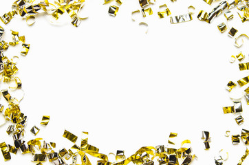 Golden confetti and foil tape on white background. Frame, copy space, flat lay.