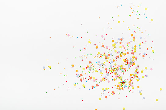 Sugar sprinkle dots on white background. Sweet decoration for cakes. Top view, copy space.