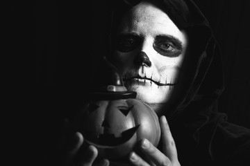 Man with halloween skull makeup and a pumpkin lantern in his hands-black and white with big copyspace