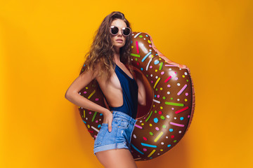 Side view of attractive young female in swimwear, trendy sunglasses holding donut-shaped swim ring and looking at camera while standing on yellow background