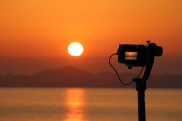 Videos Camera on a Gimbal Stabilizer tripod on the beach. Red sky sunset