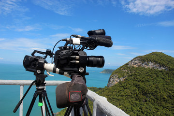 video camera on a tripod on top of the mountain. Ocean and blue sky background.