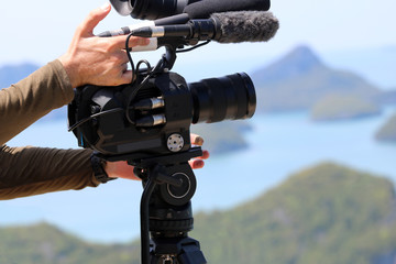 videographer holding the video camera on a tripod on top of the mountain