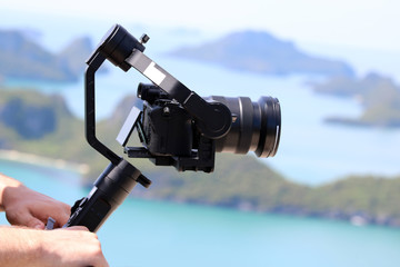 Camera Gimbal Stabilizer on top of the mountain. Ocean and blue sky background