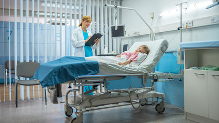 Sick Little Girl Lies on a Bed In the Hospital, Friendly Doctor Writes Medical Record/ Data into Clipboard. Cute ill Child is Taken Care in the Modern Pediatric/ Children Ward.