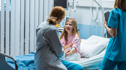 Cute Little Girl Sits on a Hospital Bed and Talks with Friendly Woman Doctor Taking Blood Test. Children's Hospital Pediatric Ward. Top Quality Health Care.