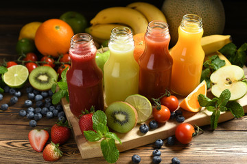 Various fresh fruits and vegetables smoothies in bottles