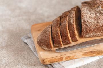 Fototapeta Fresh sliced loaf of rye bread on the wooden cutting board background obraz