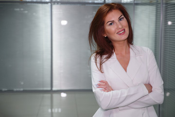 young smiling businesswoman in corridor of office