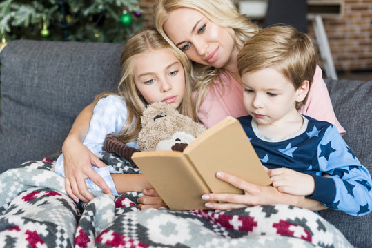 happy young mother reading book with cute kids in pajamas at christmas time