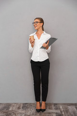 Beautiful business woman standing over grey wall background holding clipboard drinking coffee.