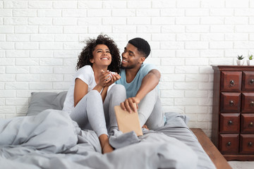 Black guy and girl drinking tea in bed early in morning