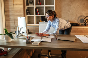Businesswoman in her office.She sitting at the desk and using computer.