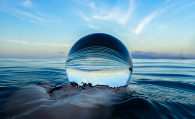 Ocean Surface Ripples and Clouds in Sky Captured in Glass Ball