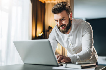 Bearded smiling businessman in shirt is typing on laptop. Man, manager works in office on computer, analyzes information