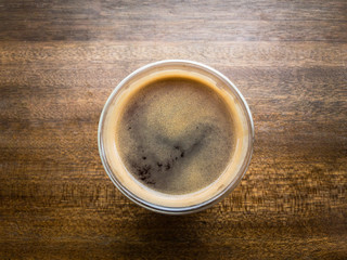 Hot americano coffee on wooden table from top angle close up.