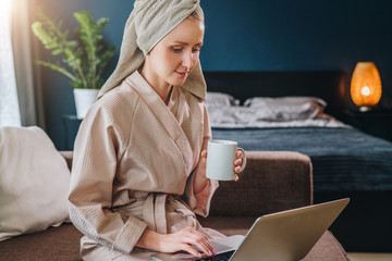 Morning. Young woman in bathrobe and towel on her head sits in room on couch, drinks coffee and uses laptop.