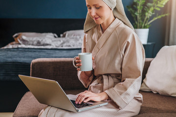 Young woman in bathrobe and towel on her head sits in room on couch, drinks coffee and uses laptop. Morning, girl after shower drinks tea and works on computer. Freelancer works at home.