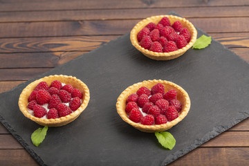 Tartlet with cream and fresh raspberries, served on a slate plate.