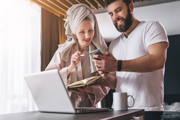 Young couple, woman in bathrobe and towel on her head, stands in kitchen near table with laptop. Freelancers work home.