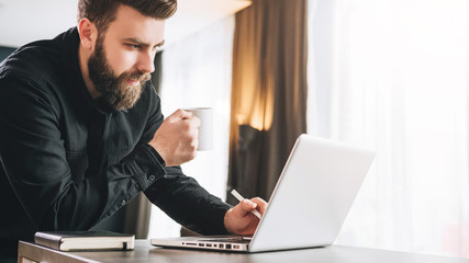 Bearded smiling businessman is standing near table, is drinking coffee, using laptop. Man works in office on computer.